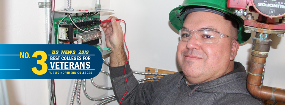 US News 2019 No. 3 Best Colleges for Veterans, public northern colleges. Image of adult male student with green hardhat and safety glasses using multimeter.